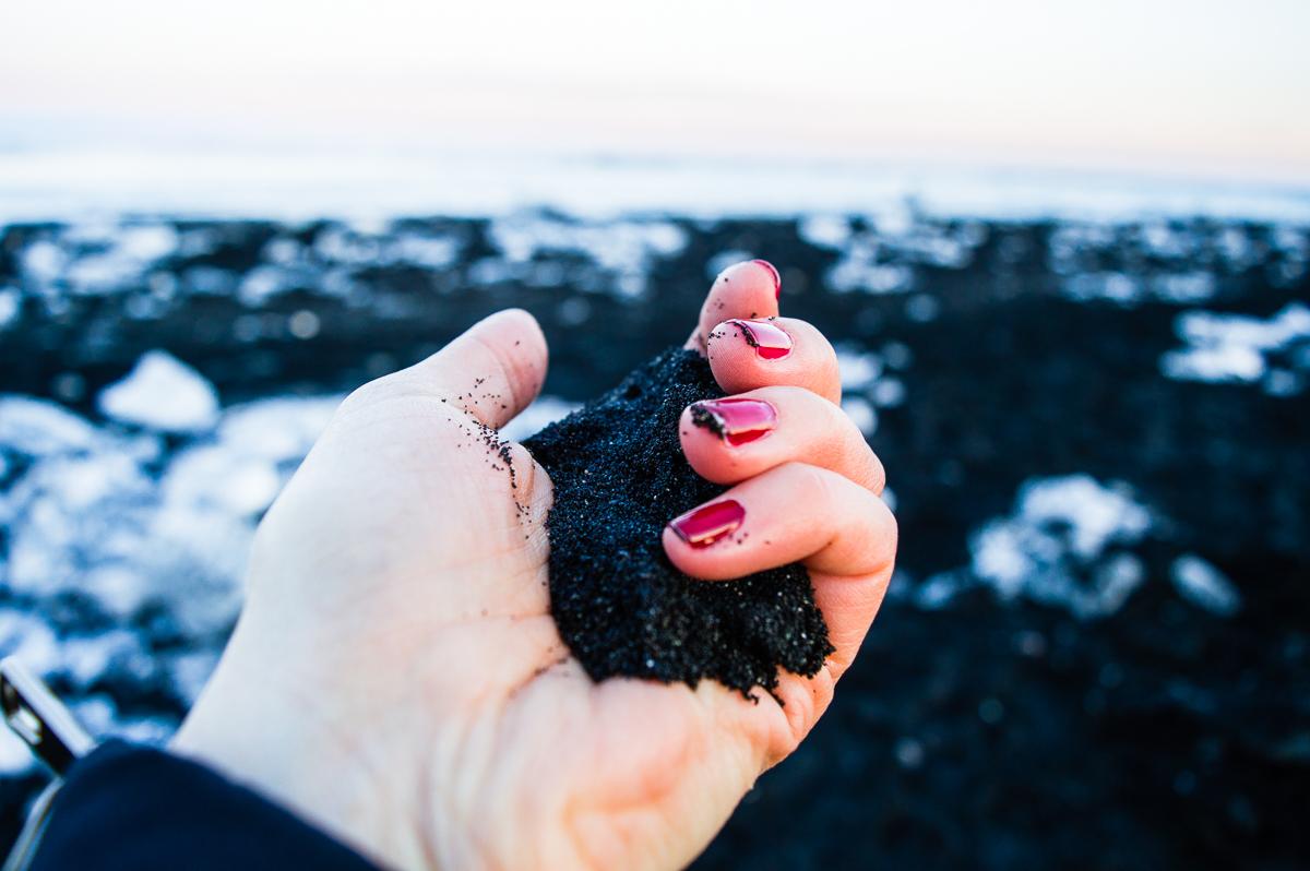 main tenant du sable noir de la plage diamond beach